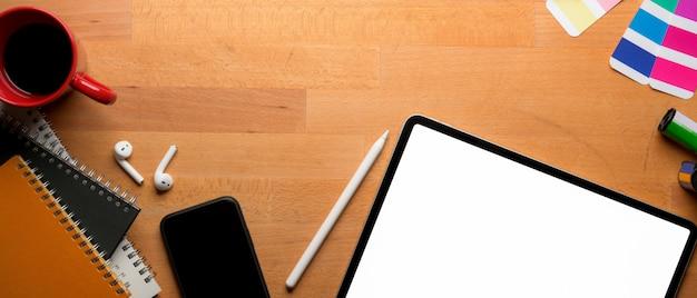 Дизайнерское рабочее пространство с макетом планшета, расходными материалами и местом для копирования