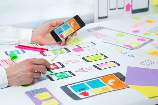 Designers develop and create a project of applications to mobile phones.