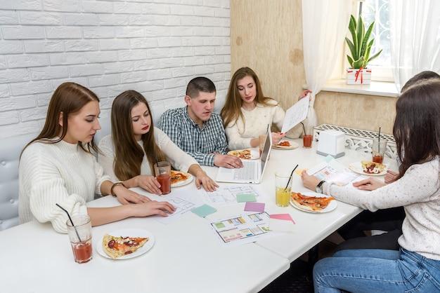 Дизайнеры обсуждают проект дома во время обеда в офисе