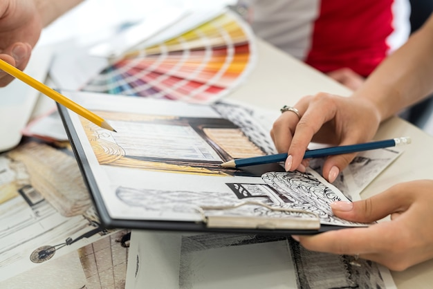Designers working with apartment sketch and colour pattern close up