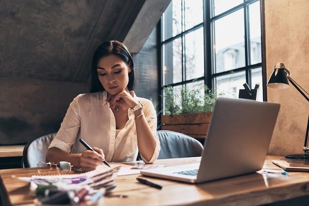 Дизайн новой одежды. красивая молодая женщина, работающая над эскизами, сидя в своей мастерской