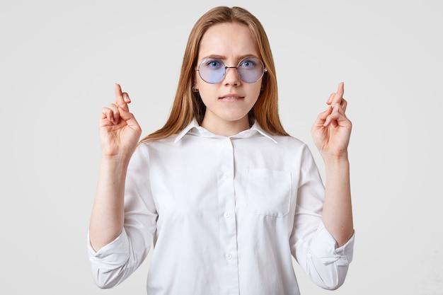 Желанная молодая женщина держит пальцы скрещенными, надеется на удачу, одета в белую рубашку, модные оттенки, кусает губы, надеется, мечты сбываются, изолированные на белом