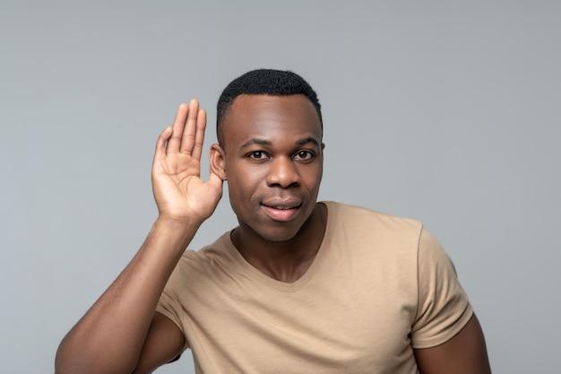 듣고 싶은 욕망. 밝은 회색 배경에 귀 근처 손바닥으로 관심을 듣고 젊은 흑인 남자