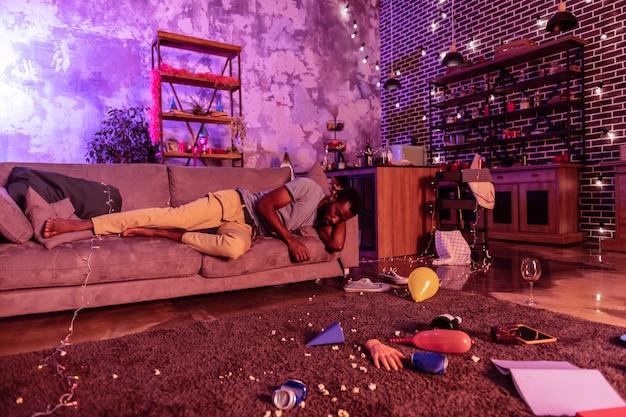 生きたいという願望。酔ったアフリカ系アメリカ人の男がジャンクで覆われた床に汚いコーチの落下