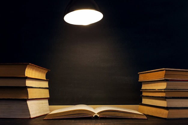 Desk against the background of the chalk board, books in the dark under the light of a lamp.