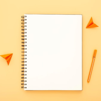 Desk arrangement with empty notepad on orange background