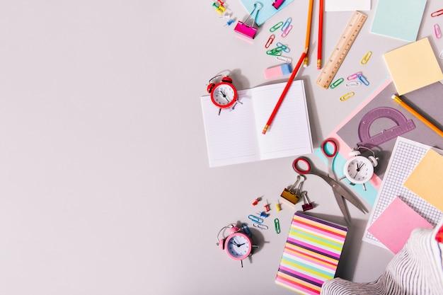 Письменный стол со школьными принадлежностями и красочными будильниками.