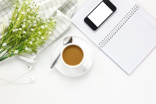 トップビュービジネスオフィスdesk.cupのコーヒーと携帯電話、アイフォーン、ノート、白いオフィスの机のコピースペースで美しい白い花。