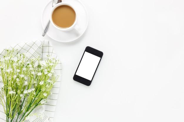 トップビュービジネスオフィスdesk.cupのコーヒーと携帯電話、白いオフィスの机のコピースペースで美しい白い花。