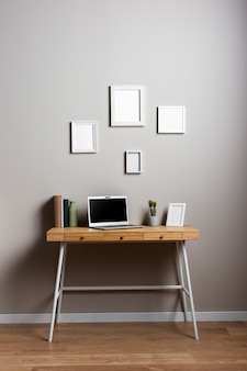 Desk design with laptop and frames mock-up