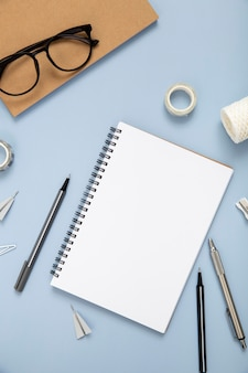Desk elements on blue background with empty notebook