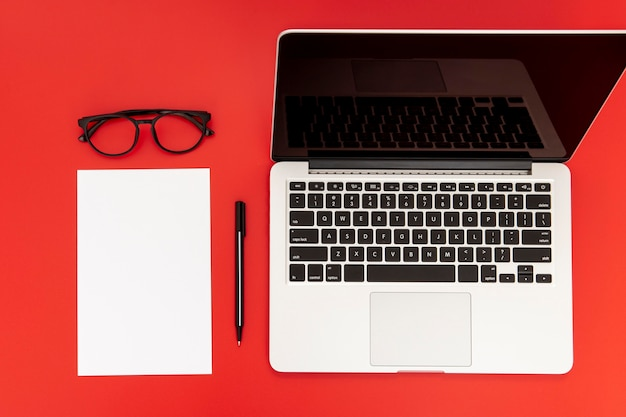 Desk elements with empty notebook on red background