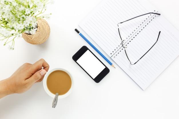 トップビュービジネスオフィスdesk.handビジネスマンは、コーヒーと携帯電話、眼鏡、コーヒー、ノート、鉛筆、美しい白い花を白いオフィスデスクにコピースペースで触れる。