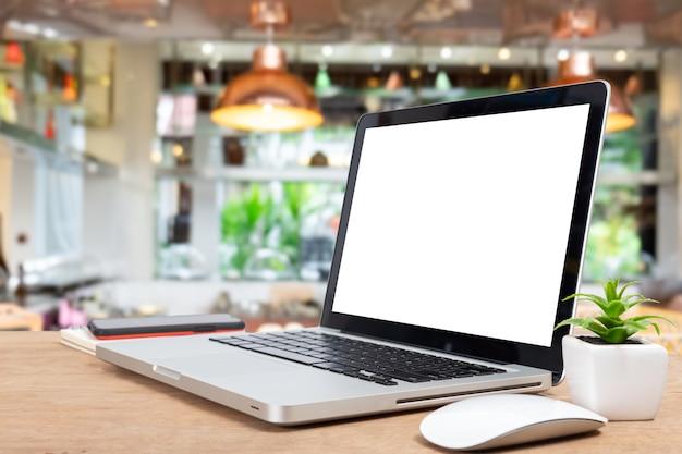 테이블에 빈 화면이 있는 데스크 노트북은 편집에 사용되는 보케 배경이 있는 배경을 흐리게 합니다.