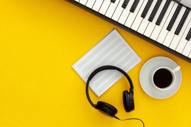 Desk of musician for songwriter work set with headphones and synthesizer