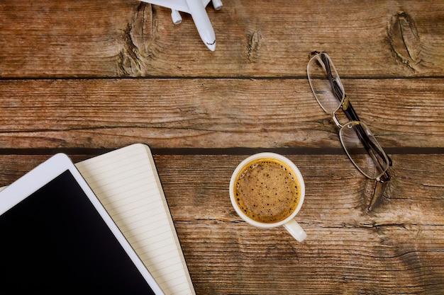 デジタルタブレットのメモ帳、木製のフラットレイにエスプレッソコーヒーとデスクオフィスの上面図