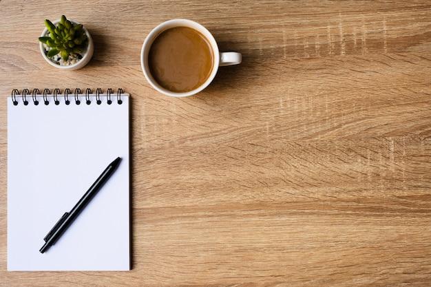 나무 테이블에 빈 메모장 및 커피 컵 책상 사무실