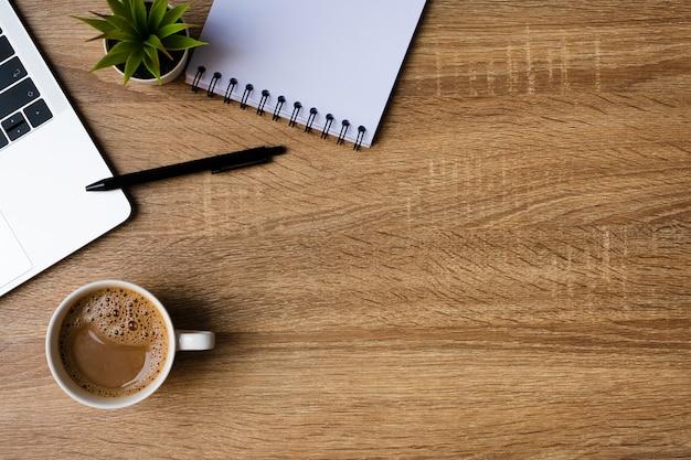 나무 테이블에 노트북, 빈 노트북 및 커피 컵 책상 사무실