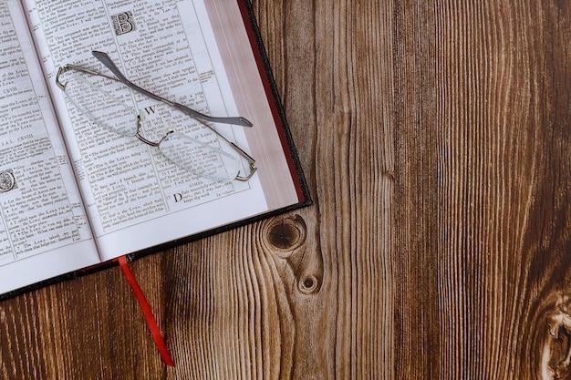 机のテーブルは、眼鏡で聖書のクローズアップの祈りの時間を開きました