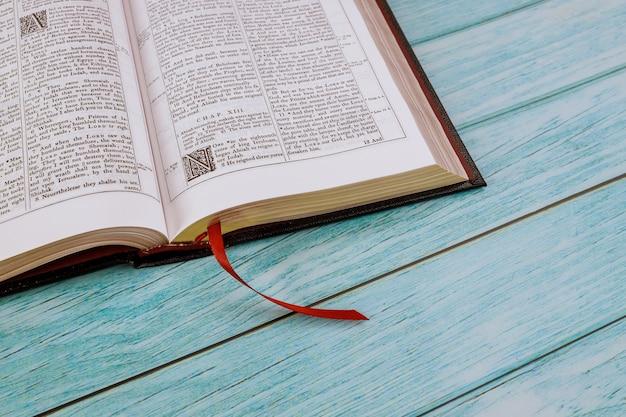 机のテーブルが聖書を開いたクローズアップの祈りの時間
