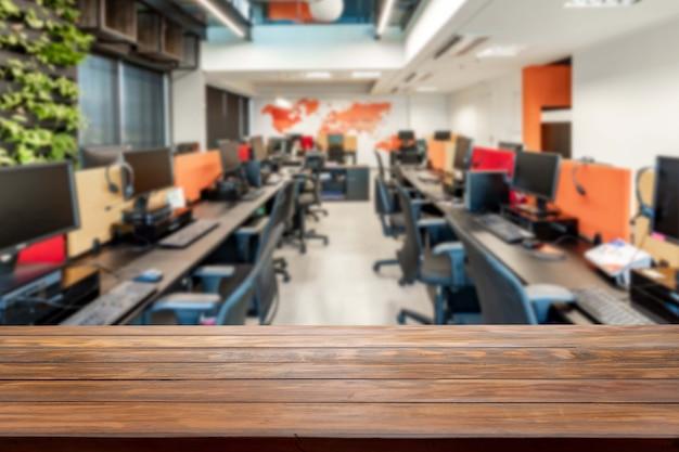 Стол в затуманенном офисе с компьютерами в фоновом режиме.