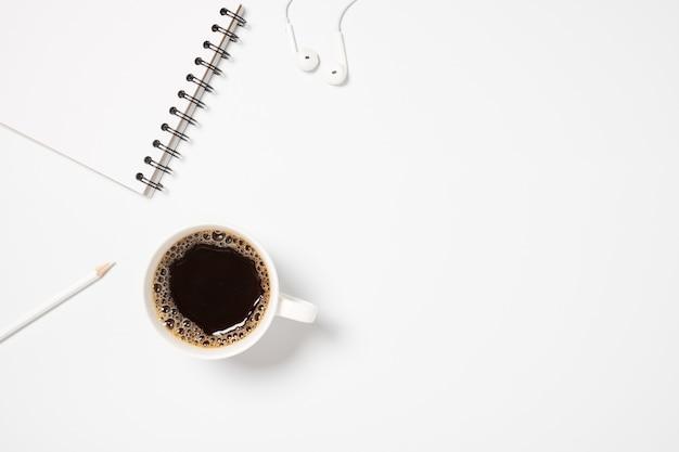 흰색 바탕에 커피 컵, 노트북 및 헤드폰 데스크 탑보기.