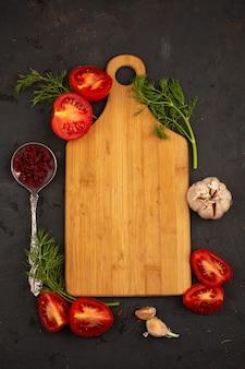 Стол овощей нарезанных спелых свежих помидоров и зелени с чесноком на темном полу