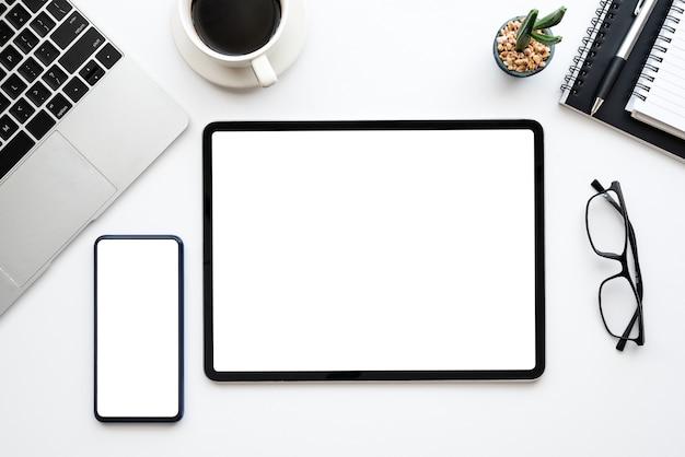 タブレット、スマートフォンの空白の白い画面とラップトップコンピューターとデスクの白いワークスペース