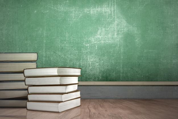 黒板の背景を持つ書籍のスタックとデスク