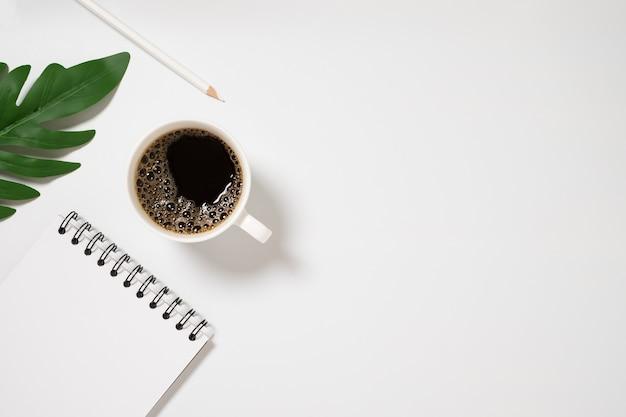 빈 노트북 및 흰색 배경 평면도에 커피 컵 책상.
