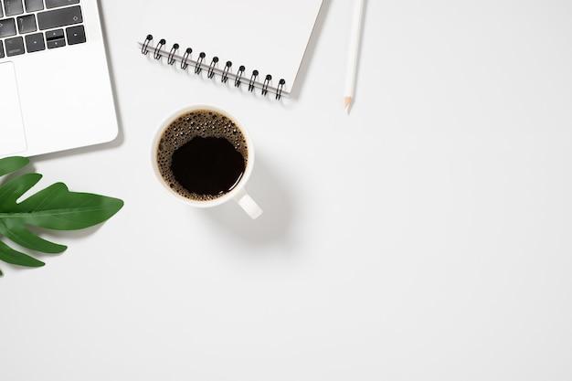 Стол с пустой тетрадью, ноутбуком и кофейной чашкой на белом фоне вид сверху.