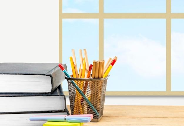 Стол с книгой и канцелярскими принадлежностями с фоном оконного стекла. снова в школу концепции