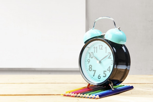 Desk with clock and row of colored pencils