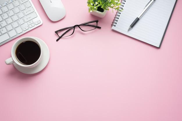분홍색 배경에 커피 키보드 노트북 안경 책상. 공간을 복사하십시오.