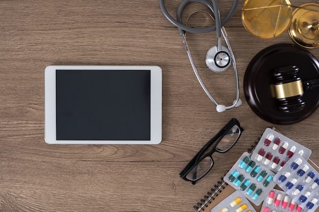 Стол с молотком, очки, планшет и лекарства