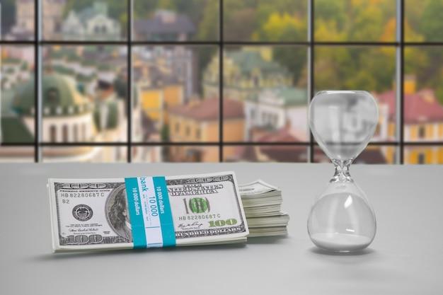 Стол с песочными часами и долларами. связка наличных денег и песочных часов. столик клерка в дневное время. недвижимость по низким ценам.