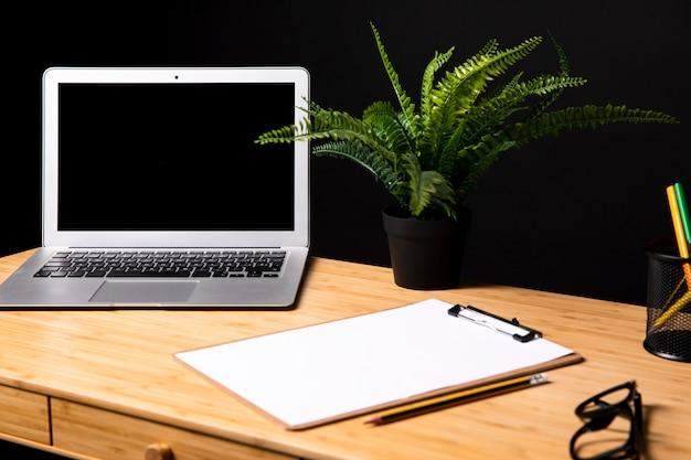 ノートパソコンとクリップボードのモックアップを備えたデスク