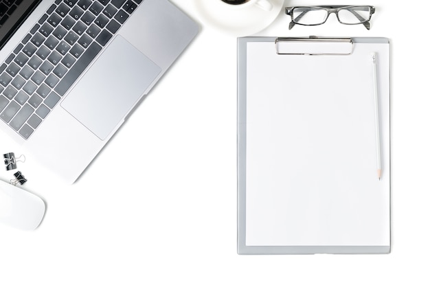 Desk with laptop, eye glasses, blank notebook and a cup of coffee isolated on white background. top