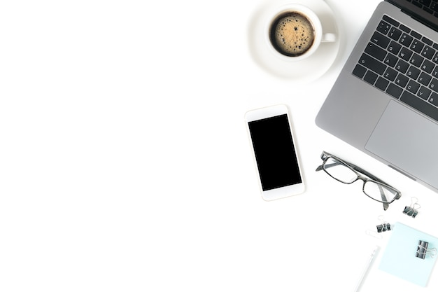 Desk with laptop, eye glasses, notebook and a cup of coffee isolated on white background. top view w