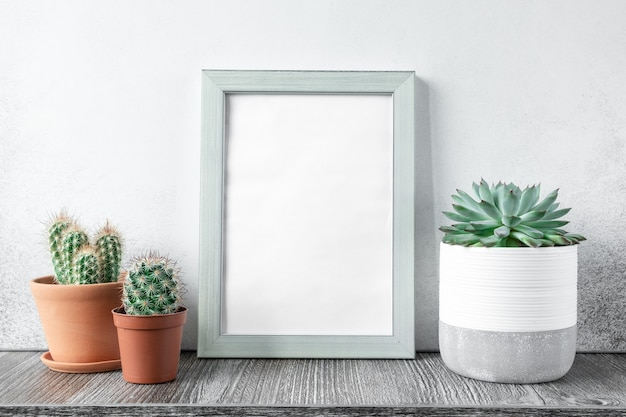 다른 세라믹 냄비에 식물이있는 나무 선반에 사진 프레임을 모의하는 책상. 가정 원예