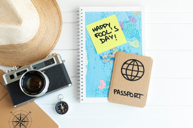Desk with travel items such as camera, compass, hat and map next to a cardboard passport as a joke for fool's day celebration. space for text.