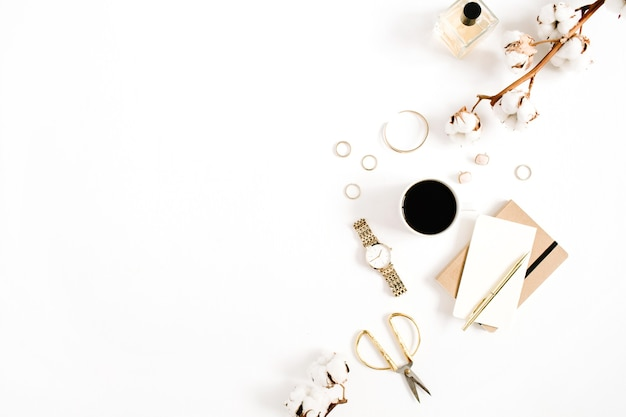 白い背景に女性のアクセサリー コレクションの黄金の時計、はさみ、コーヒー カップ、ノート、綿の枝を持つデスク。平置き