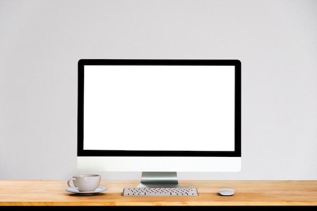 Концепция работы стол. рабочее пространство с настольным компьютером, канцелярскими товарами, комнатными растениями и чашкой кофе в офисе.
