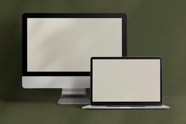 緑の背景にデスクトップとラップトップ画面のコンピューターデジタルデバイス