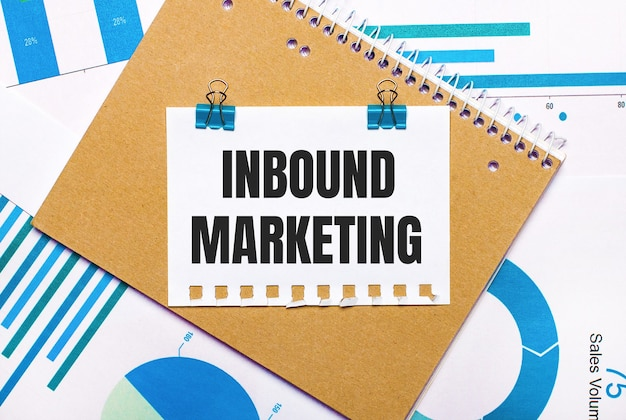 On the desktop are blue and light blue graphs and diagrams, a brown notebook and a sheet of paper with blue clips and inbound marketing text