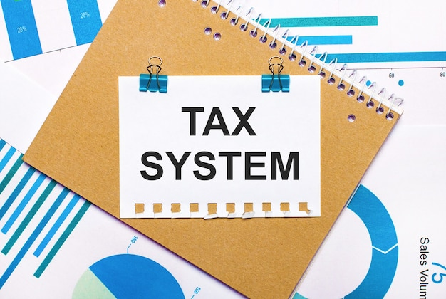 On the desktop are blue and light blue graphs and diagrams, a brown notebook and a sheet of paper with blue clips and tax system text. view from above. business concept