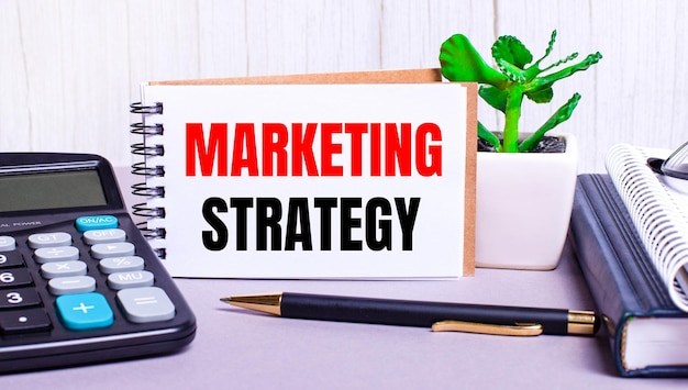 On the desktop are a calculator, diaries, a potted plant, a pen and a notebook with the text marketing strategy. business concept. workplace close up