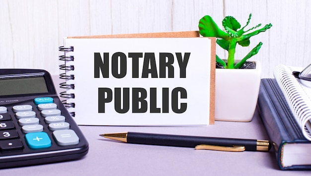 On the desktop are a calculator, diaries, a potted plant, a pen and a notebook with the text notary public. business concept. workplace close up