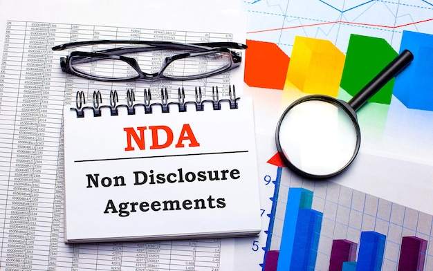 On the desktop are glasses, a magnifying glass, color charts and a white notebook with the text nda non disclosure agreements. business concept. view from above