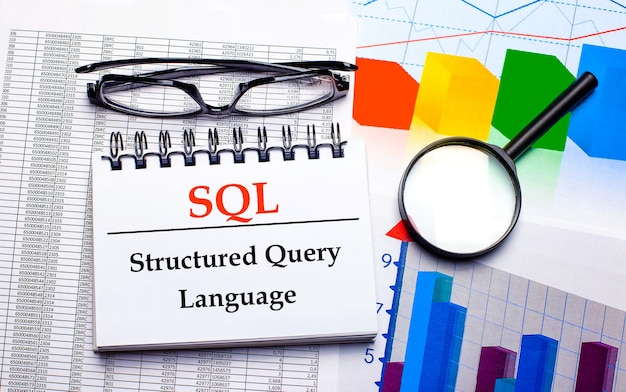 On the desktop are glasses, a magnifying glass, color charts and a white notebook with the text sql structured query language. business concept. view from above